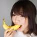 皮ごとバナナを食べる女性