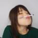 鼻と口の間にペンを挟む女性