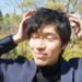 強風で髪型を気にする男性