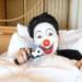 ベッドの上から銃口を向けるピエロ