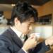 コーヒーを飲みながらニュースをチェックするビジネスマン