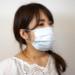無表情でマスクを装着する女性